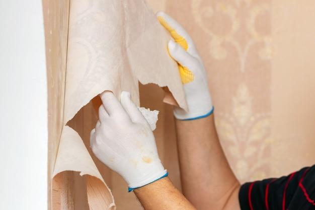 De meester verwijdert oud behang van de muur. reparatie van appartementen
