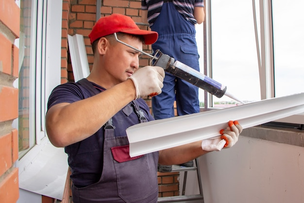 De meesterarbeiders installeren vensterbankreparatie in woningbouw