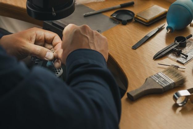 De meesterjuwelier houdt het werkinstrument in zijn handen en maakt sieraden op zijn werkplek in het juweliersatelier.