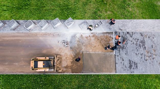 De meesters leggen straatstenen. stoepreparatie. wegwerkers luchtfoto.