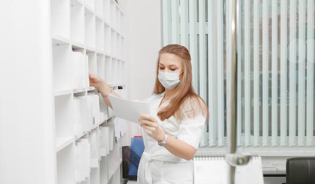 De meisje-administrateur van de medische kliniek zoekt een patiëntenkaart in de la van het rek