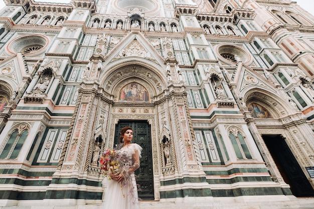 De meisje-bruid is met een prachtig bloemenpatroon als masker in florence, stijlvolle bruid in een trouwjurk die met een masker in de oude binnenstad van florence staat. modelmeisje in florence.