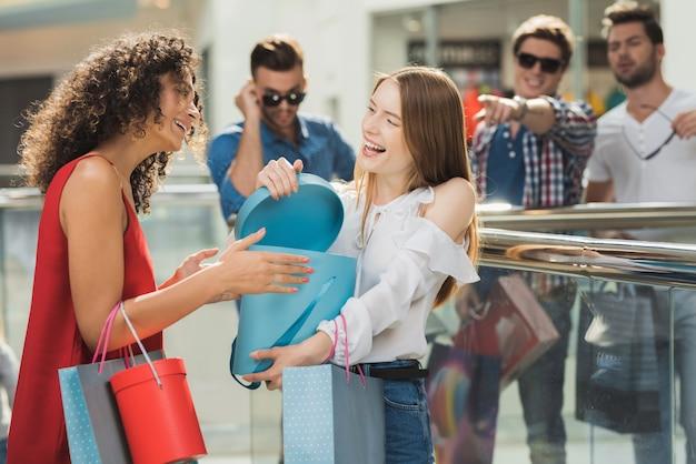 De meisjes laten elkaar de kleding zien die ze hebben gekocht.
