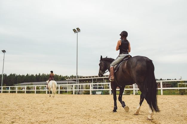 De meisjes rijden op paarden