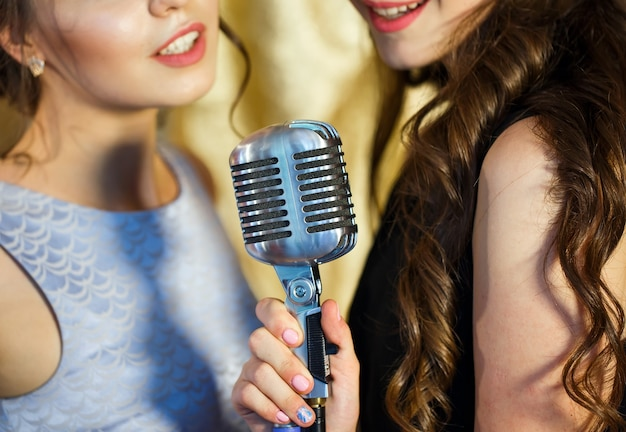 De meisjes zingen karaoke in het restaurant.