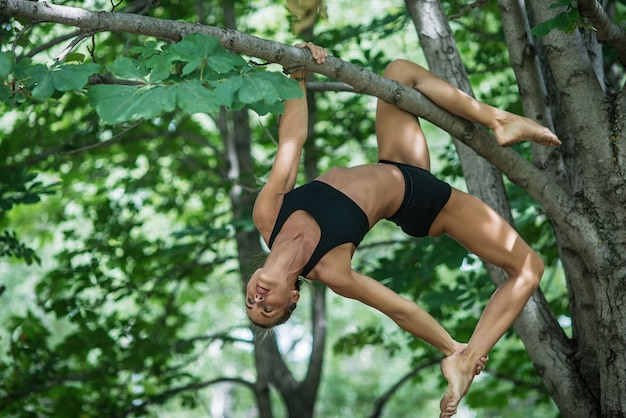 De meisjesacrobaat voert acrobatisch element op de boom uit. vrouw die zich bezighouden met gymnastiek