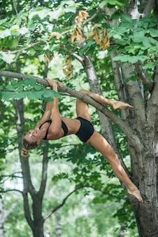 De meisjesacrobaat voert acrobatisch element op de boom uit