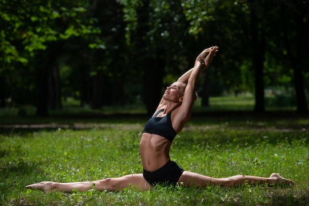 De meisjesacrobaat voert acrobatisch element op het gras in het park uit