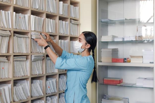 De meisjesadministrateur van de medische kliniek vindt de benodigde patiëntenkaart in de la van het rek en controleert de correspondentie van de achternaam. medisch centrum