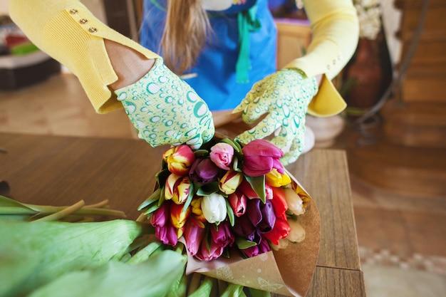 De meisjesbloemist verpakt mooie tulpen in een bloemenwinkel in kraftpapier-document