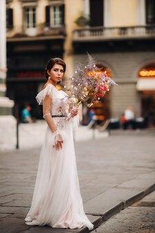 De meisjesbruid is met een prachtig bloemenpatroon als masker in florence, stijlvolle bruid in een trouwjurk die met een masker in de oude binnenstad van florence staat. modelmeisje in florence.