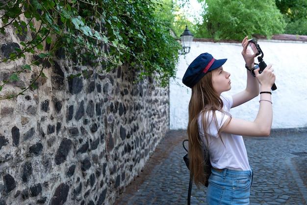 De meisjesfotograaf zoekt een goede invalshoek voor het maken van foto's op straat.