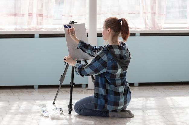 De meisjeskunstenaar zit op de vloer van marmeren tegels. vrouw tijdens het tekenen van olieverfschilderijen.