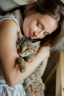 De meisjeskunstenaar zit op haar werkplek en schildert portretten in aquarellen. afgewerkte werken hangen aan de muur. ze heeft een grijze kat in haar armen.