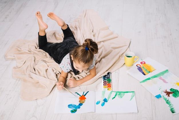 De meisjestekening door waterkleuren op papier trekt dichtbij en liggend op vloer