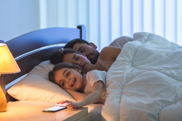 De meisjestelefoon bij de slapende ouders op het bed