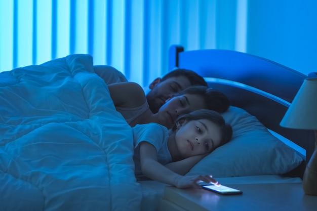De meisjestelefoon dichtbij de slapende ouders op het bed. nachttijd