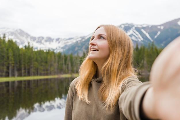 De meisjestoerist die selfie in het bergmeer neemt. opkijken en glimlachen. reizen en actief leven concept. buitenshuis