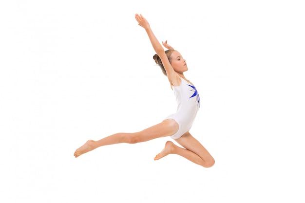 De meisjesturner in witte trico in volledige hoogte presteert in een witte sprong die op een witte oppervlakte wordt geïsoleerd