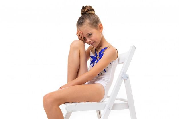 De meisjesturner in witte trico in volledige hoogte zit op een witte stoel
