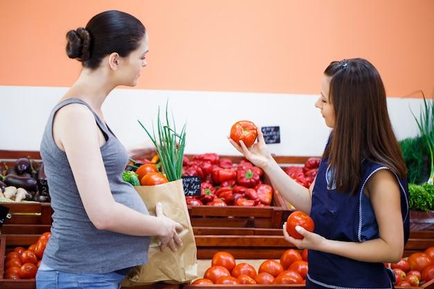 De meisjesverkoper geeft een document zak met aankopen aan een zwangere vrouw bij een groentewinkel