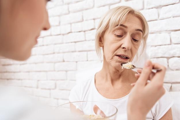 De meisjesverpleegster voedt een zieke oude vrouw in het ziekenhuis