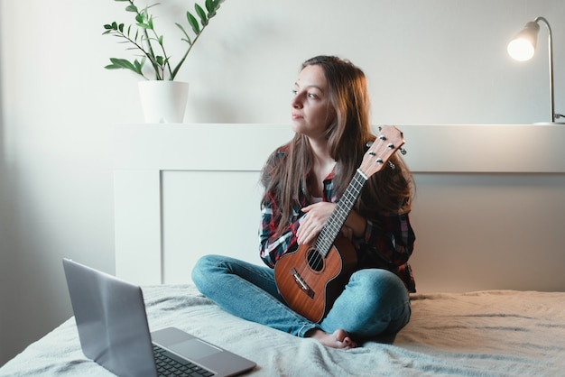 De meisjeszitting thuis leert ukelele spelen met behulp van online lessen.