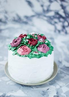 De melkachtige meisjescakeplak verfraaide groene bladeren en leliebloemen, cake die als bloemboeket wordt verfraaid, het decor van de de lentecake