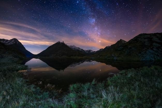 De melkwegboog en de sterrenhemel weerspiegeld op het meer op grote hoogte in de alpen.