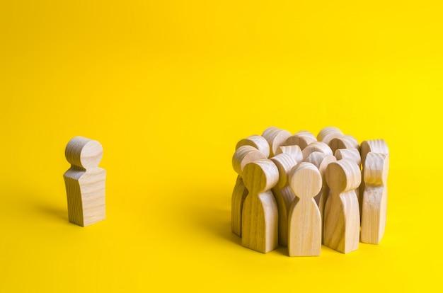 De menigte houten figuren van mensen staat in de verte en kijkt naar de rode man. slechte zaken
