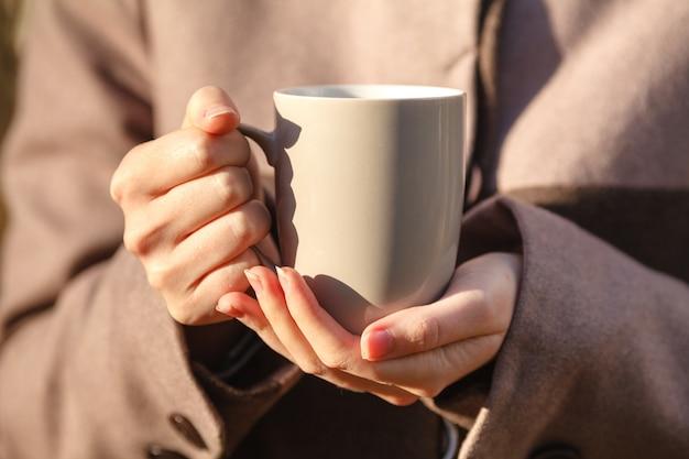 De mening van de close-up van beschikbare kop koffie of thee in de hand van de vrouw. herfst park met bomen en gele bladeren