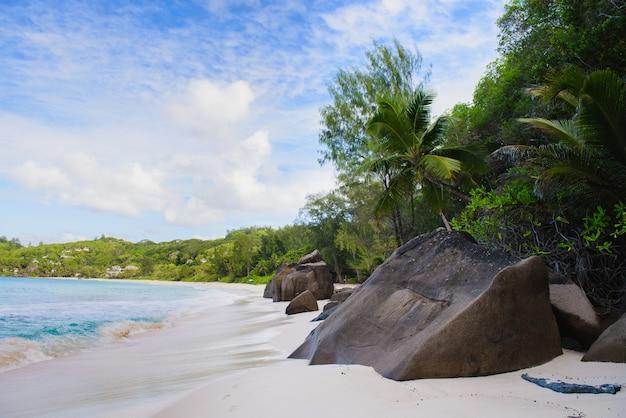 De mening van het het zandstrand van seychellen met grote stenen
