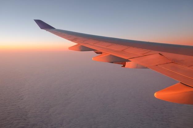 De mening van het vliegtuigvenster bij zonsondergang voor vakantieconcept