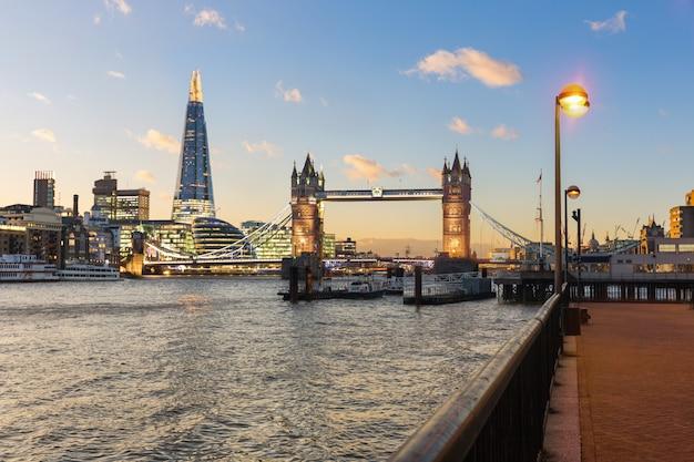 De mening van londen bij zonsondergang met torenbrug en moderne gebouwen