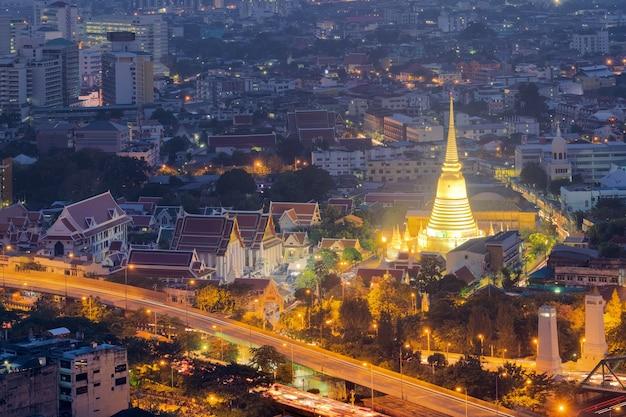 De mening van wat prayunwongsawat verlichtte gouden pagode bij nacht in bangkok, thailand