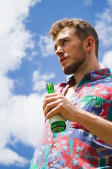De menings blonde jongen die van de bodem een bier houdt