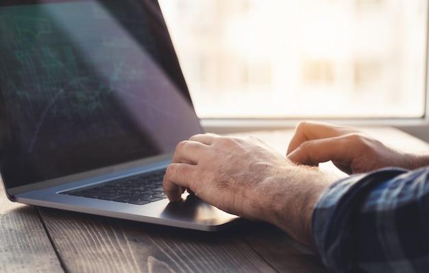 De mens analyseert en controleert de grafiek op laptop. thuiskantoor werkplek