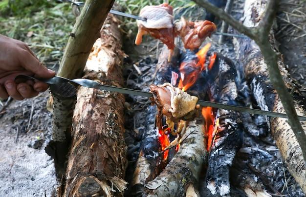 De mens bakt kip op het open vuur. grillen in het bos. toerist die buiten eet.