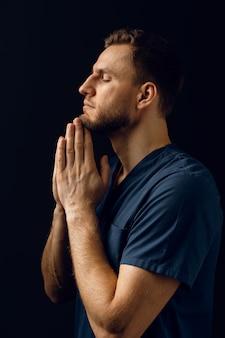 De mens bedekt zijn gezicht met zijn handen en denkt aan het leven. knappe man bid en geloof in god. orthodox christelijk geloof.