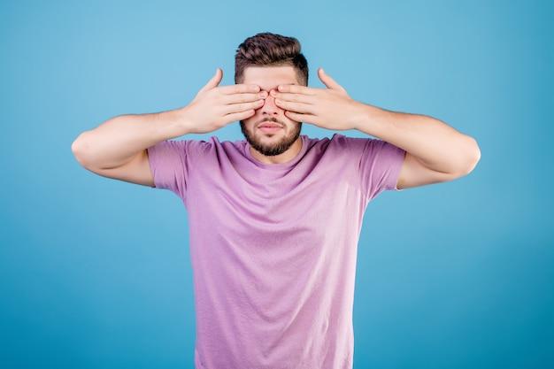 De mens behandelt ogen met handen die over blauw worden geïsoleerd