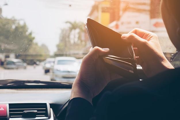 De mens bekijkt zijn lege portefeuille terwijl het drijven van auto, gevaarlijk gedrag