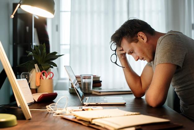 De mens beklemtoonde terwijl het werken aan laptop