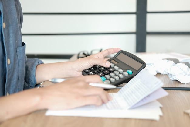 De mens berekent binnenlandse rekeningen, zakenman die met calculator saldo controleren