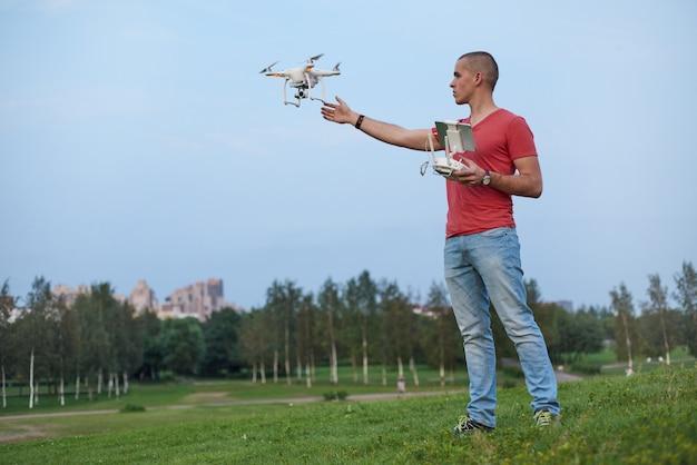 De mens bestuurt een quadrocopter in park
