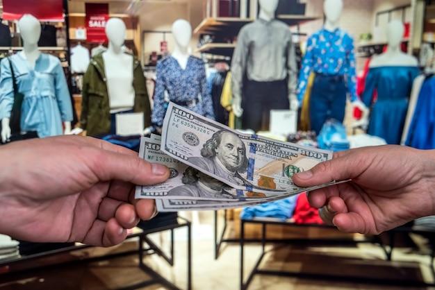 De mens betaalt in dollars voor het kopen van kleding in een winkel. winkelen concept