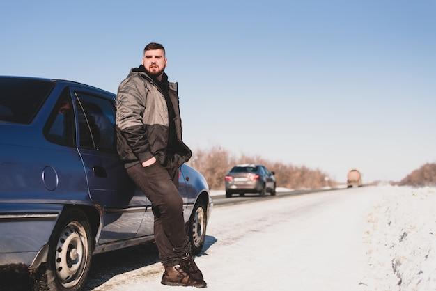 De mens bevindt zich dichtbij zijn gebroken auto in de winter