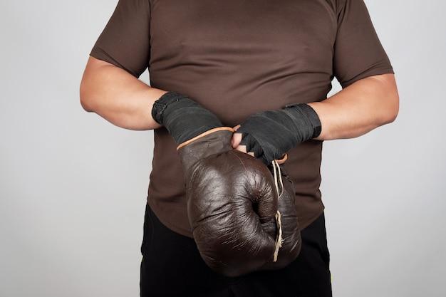 De mens bevindt zich en trekt op zijn handen zeer oude uitstekende bruine bokshandschoenen
