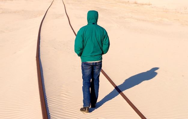De mens bevindt zich op de spoorweg in het zand
