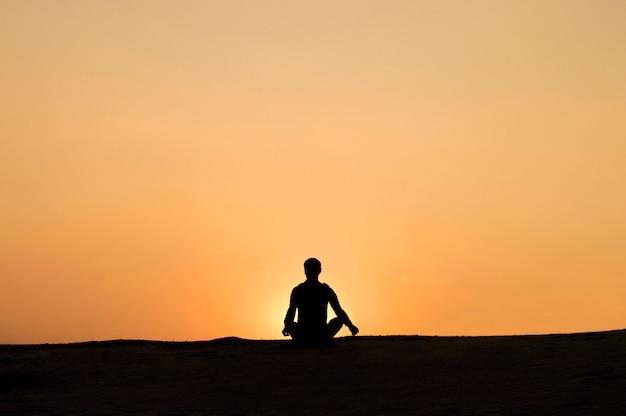 De mens bij zonsondergang ontspant het doen van yoga