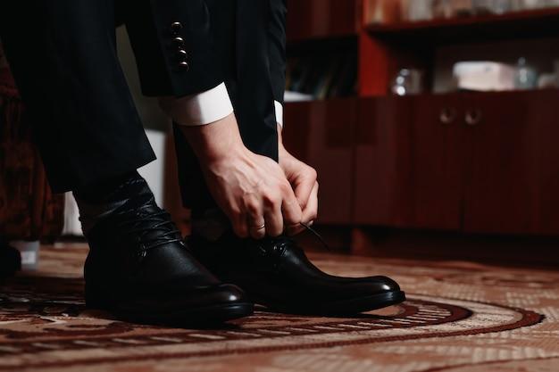 De mens bindt zijn zwarte schoenen vast